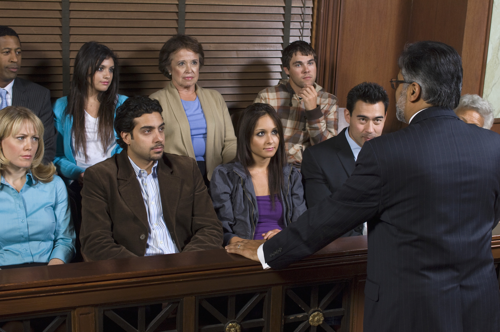 A male lawyer addressing a jury in court.
