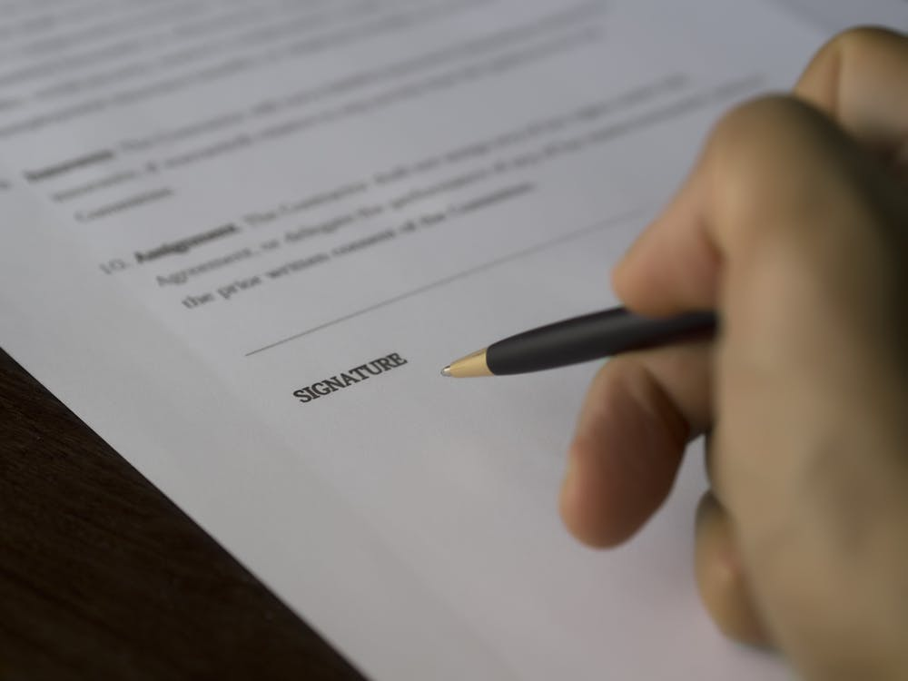 Contract being signed by a pen